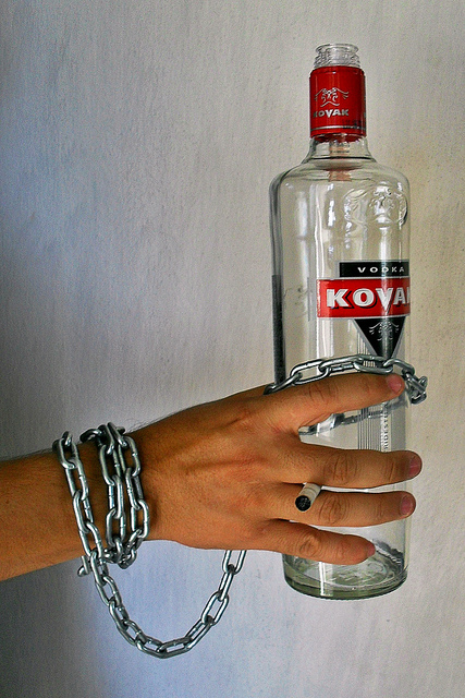 Man's wrist chained to a bottle of alcohol